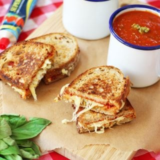 This brilliant store cupboard tomato basil soup recipe, makes a fantastic quick lunch or dinner. It's whipped up super fast using tinned tomatoes in just 20 minutes. The addition of pesto and pizza style grilled cheese sandwiches makes it really something special! http://www.tamingtwins.com