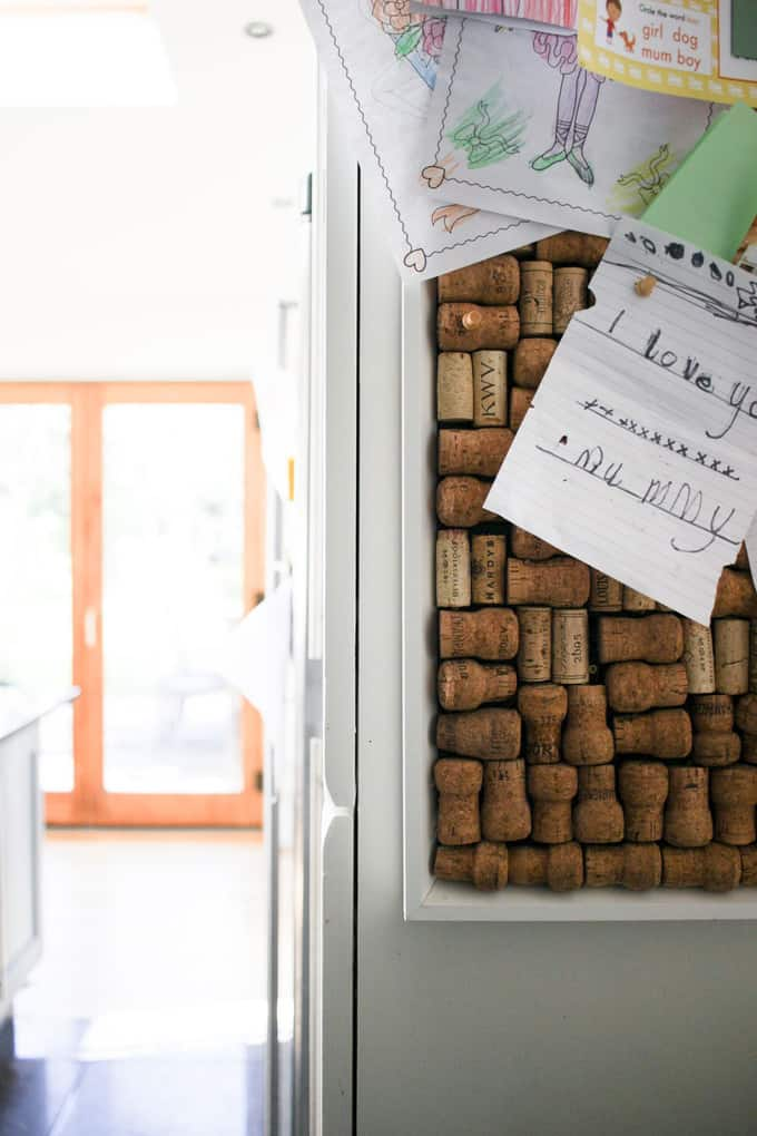 Homemade cork boards with repurposed corks. A grey kitchen tour. This light and airy kitchen, included wooden cabinets painted gray, bi-fold doors, Velux window roof lights, an Instagram photo gallery wall, black tile floor, wooden floor, HUGE island unit and heaps of other ideas for monochrome kitchen and dining areas.