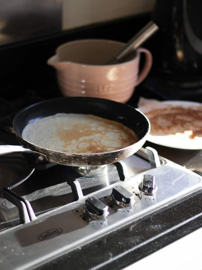 Pancake in a frying pan on a hob with a pink ceramic jug in the background.