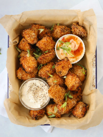 Popcorn chicken pieces with dips in a tray.