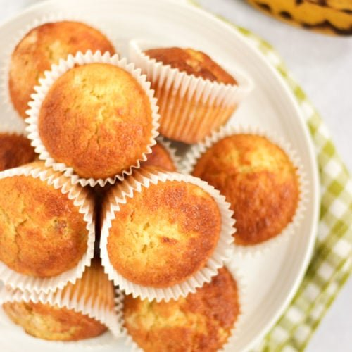Banana muffins on a white plate with green tea towel and ripe bananas
