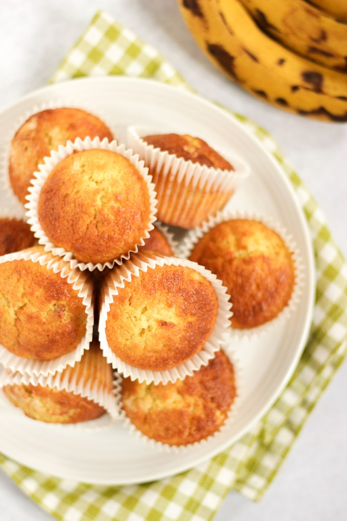 BANANA MUFFINS - JUST 5 INGREDIENTS! These simple, quick to make muffins are perfect for baking with toddlers, deliciously moist and make a yummy treat or a breakfast on the go. This moist UK recipe is easily adaptable to add peanut butter, blueberries, Nutella or chocolate chips. #tamingtwins #cookingwithkids #bananarecipes #bananamuffins #easyrecipes #muffins #ukrecipes #cupcakes
