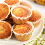 Banana muffins on a plate piled up with ripe bananas in the background