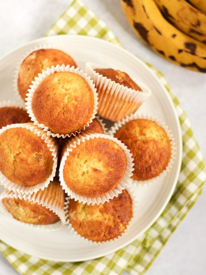 Pile of freshly baked banana muffins on a white plate in white cases