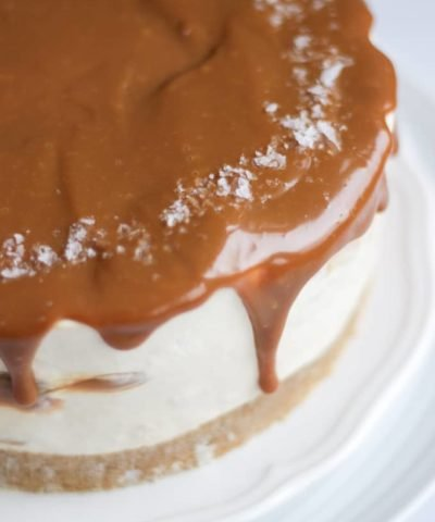 Side view of salted caramel cheesecake with dripping caramel on a white plate.