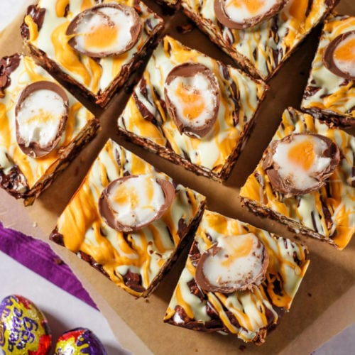 Pieces of creme egg rocky road chocolate squares on chopping board.
