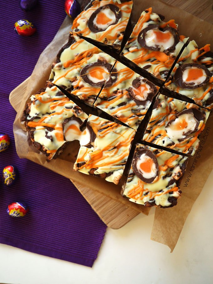 Creme Egg Rocky Road on baking paper with a purple placemat, wooden board and Mini Creme Eggs overhead.