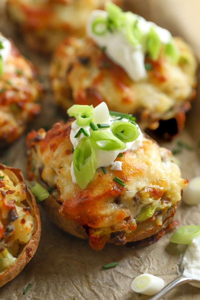 Stuffed potato skins topped with sour cream and chopped spring onions
