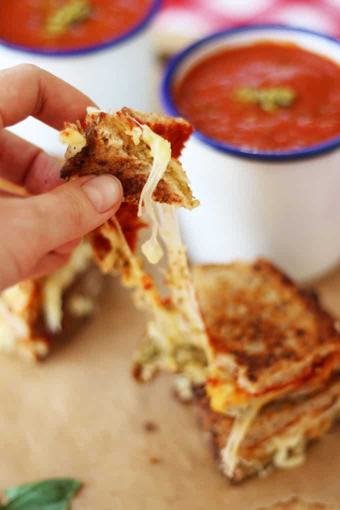 This brilliant store cupboard tomato basil soup recipe, makes a fantastic quick lunch or dinner. It's whipped up super fast using tinned tomatoes in just 20 minutes. The addition of pesto and pizza style grilled cheese sandwiches makes it really something special! https://www.tamingtwins.com