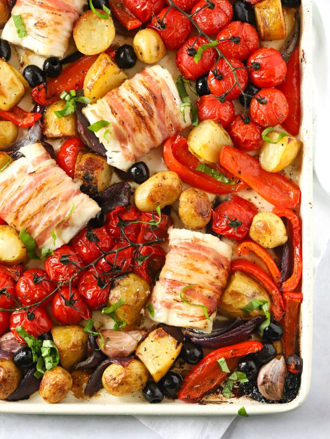 Loins of cod wrapped in bacon roasted with tomatoes, potatoes and vegetables