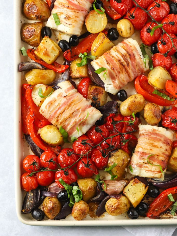 Fish wrapped in bacon with tomatoes, peppers and potatoes on a sheet pan