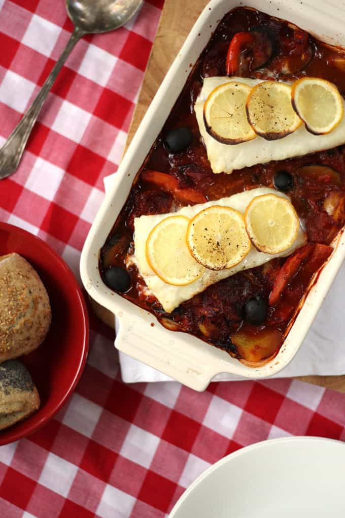 A quick and easy midweek dinner, light and fresh Italian baked cod. Packed with tomatoes, peppers and olives, this oven cooked fish recipe is also Slimming World friendly. https://www.tamingtwins.com