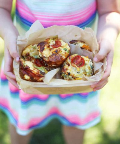 Mini Crustless Quiches with Cherry Tomatoes in a lunchbox lined with baking paper held in the hands of a little girl.