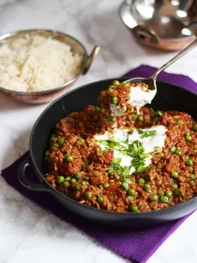 Spoon lifting up some lamb keema recipe curry with peas on a purple cloth with rice in the background.
