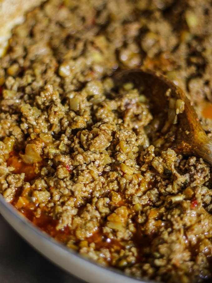Minced lamb cooking down with wooden spoon for minced lamb keema curry recipe.