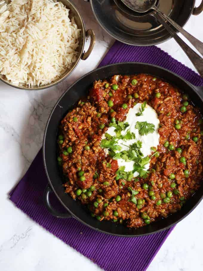 Keema recipe how to make easy lamb mince keema curry overhead shot of lamb mince curry with peas in a black pan on a purple cloth forumfinder Gallery