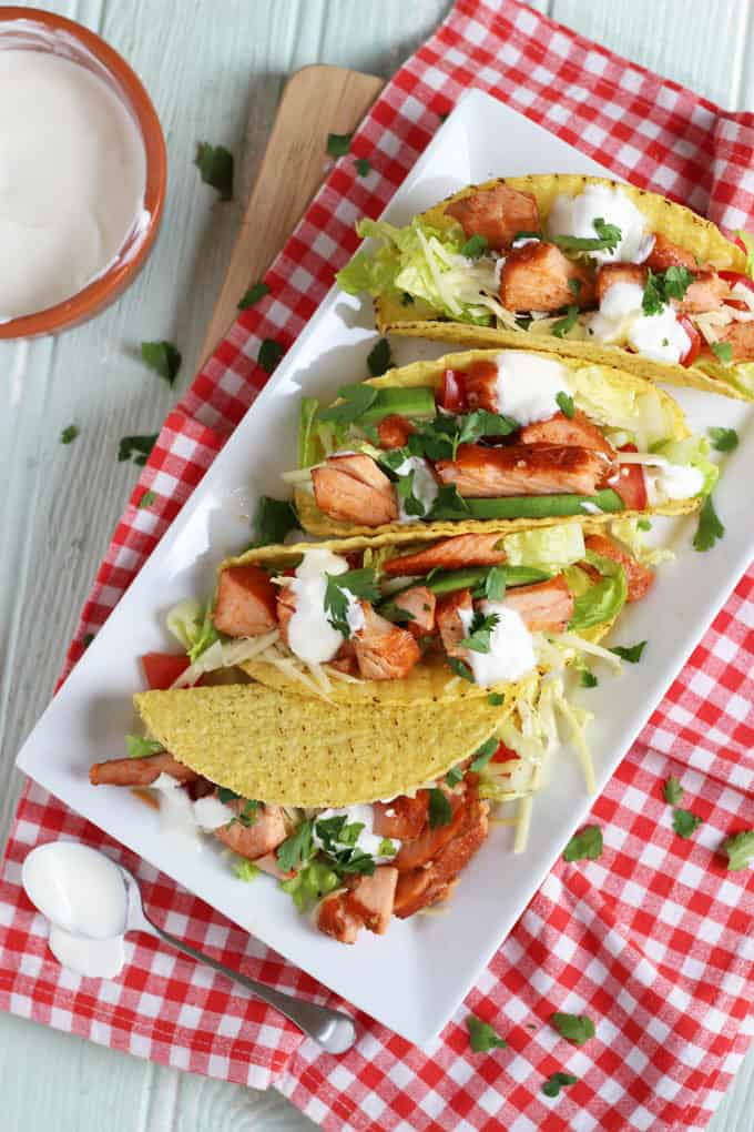 Easy, no cook salmon tacos. A perfect quick mid-week, assembly only dinner. Crispy taco shells, topped with salmon, lettuce, cheese, tomatoes, avocado and yoghurt.