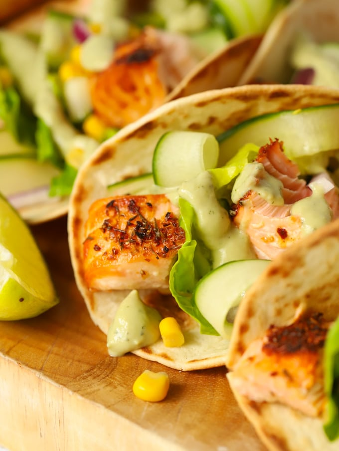 Easy salmon tacos recipe on a wooden board with cucumber and avocado dressing