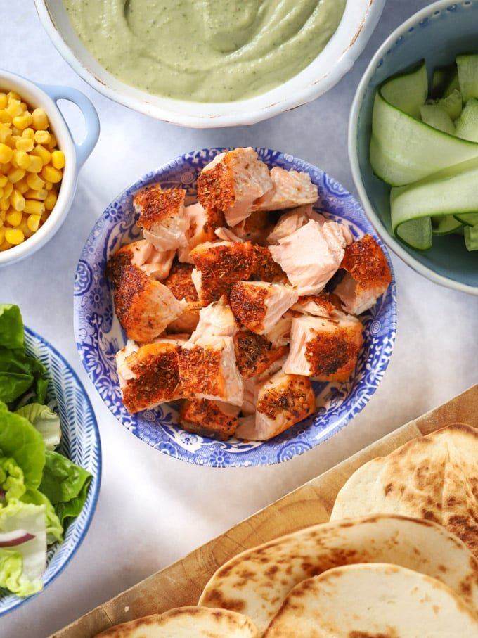 cajun fish pieces with cucumber, sweetcorn, lettuce and tortillas