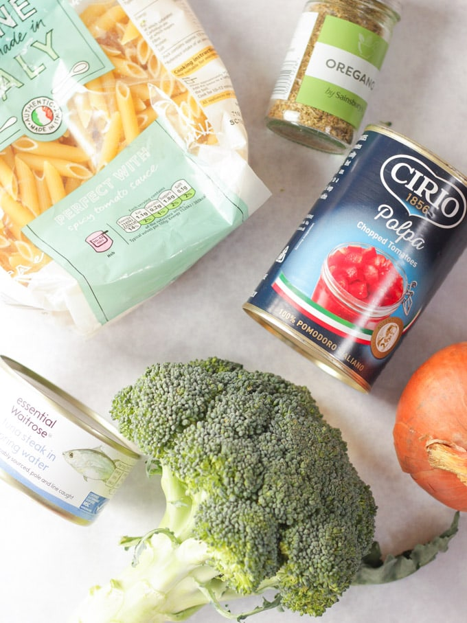 pasta, tinned tomatoes, canned fish, broccoli, onion and oregano on a marble background