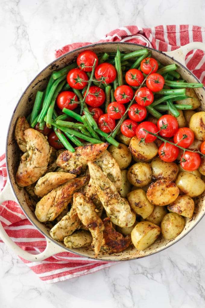 Pesto chicken bake in a dish with green beans, tomatoes and potatoes