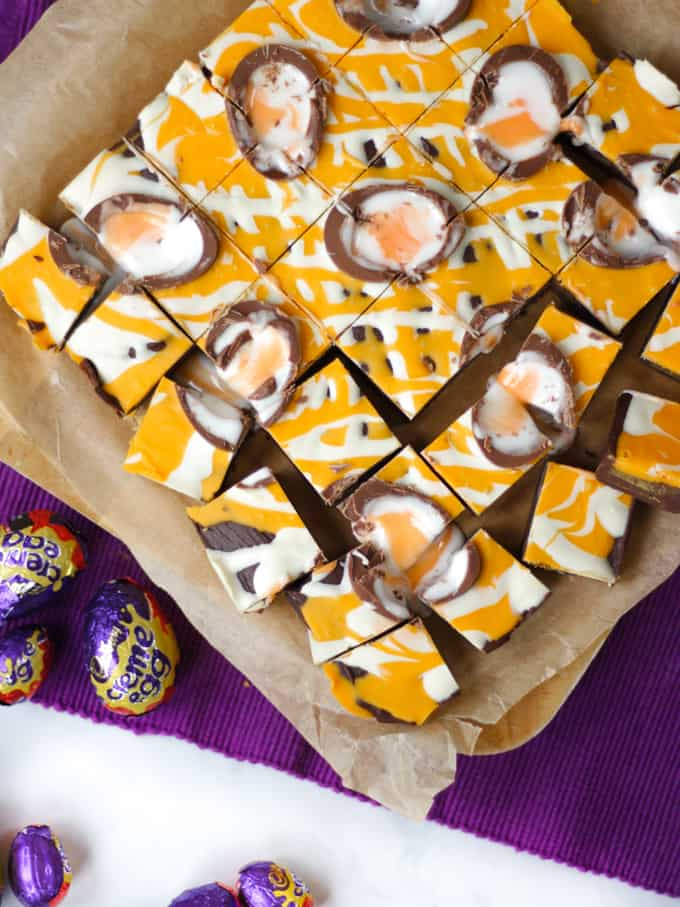 Overhead photo of yellow drizzled Creme Egg chocolate fudge cut into small squares.