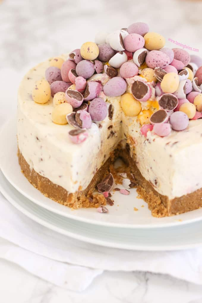 Mini Egg Cheesecake with a slice taken out on two white plates on top of a napkin.