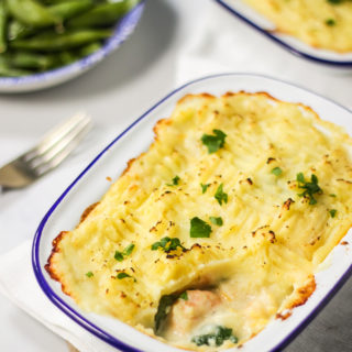 Easy fish pie in a white and blue metal dish with fork and sugar snap peas in background.