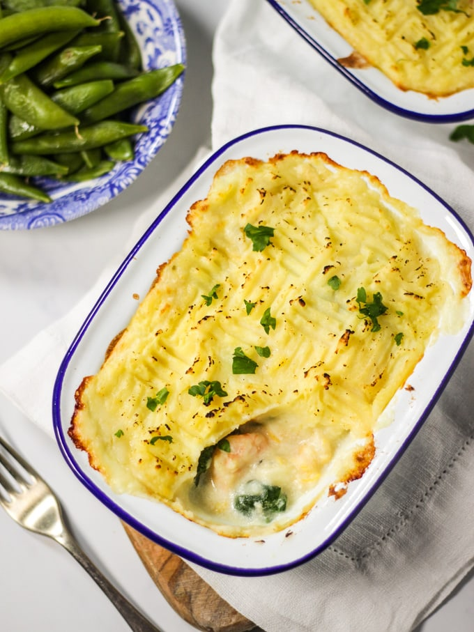 Two portions of easy fish pie sprinkled with parsley.