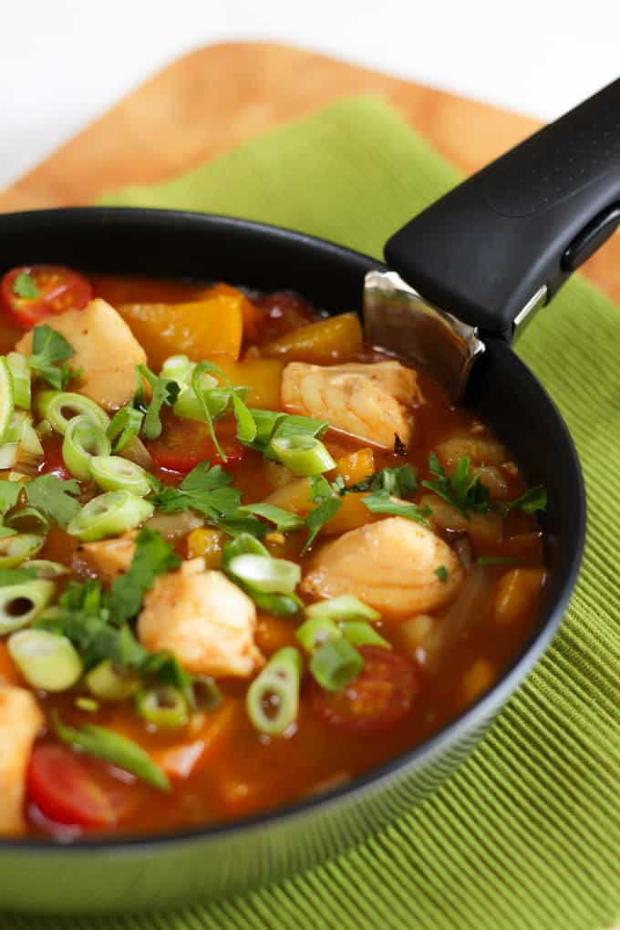Fish stew with a coconut and tomato sauce with lime wedges.