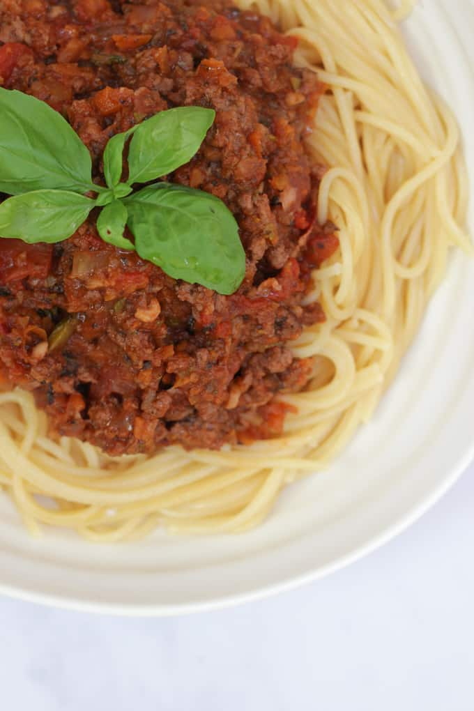 Bolognese sauce with hidden vegetables pilled on top of spaghetti, served in a white bowl with a basil leaf on top.
