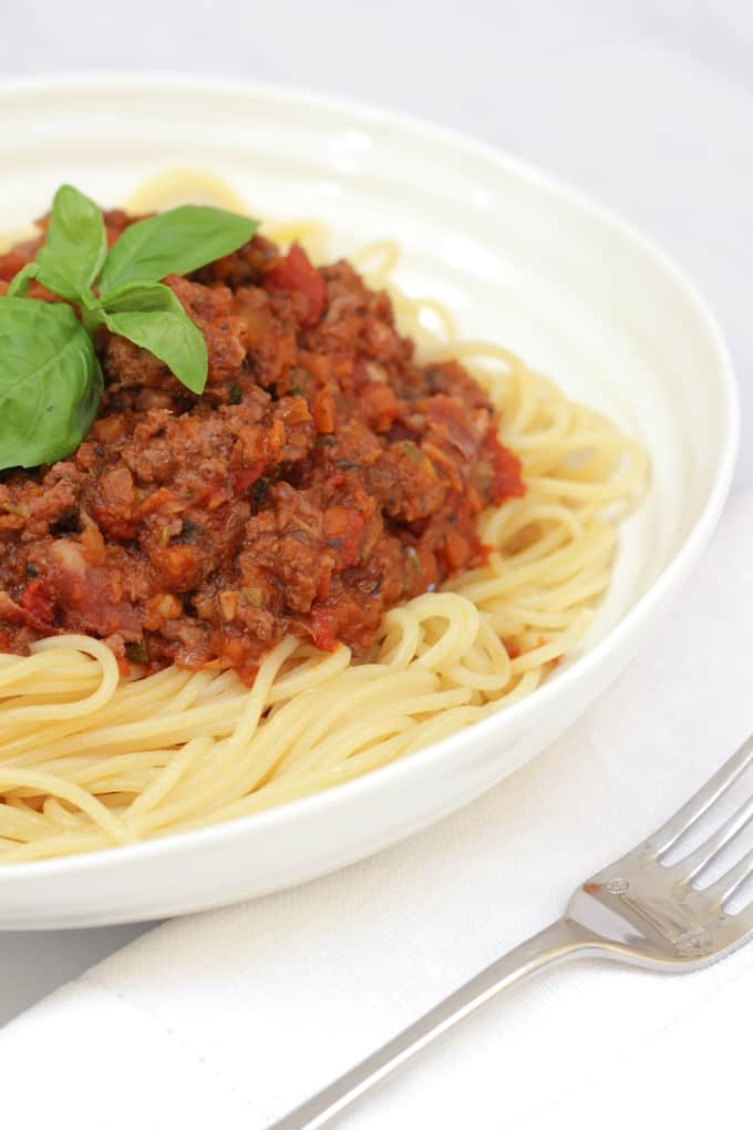 Bolognese sauce (with hidden vegetables) on top of pasta in a white bowl, with a basil leaf on top.