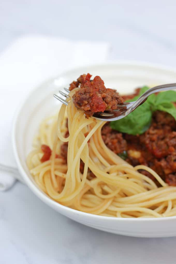 Bolognese sauce with pasta in a bowl, with a fork showing meat and pasta piled on top.