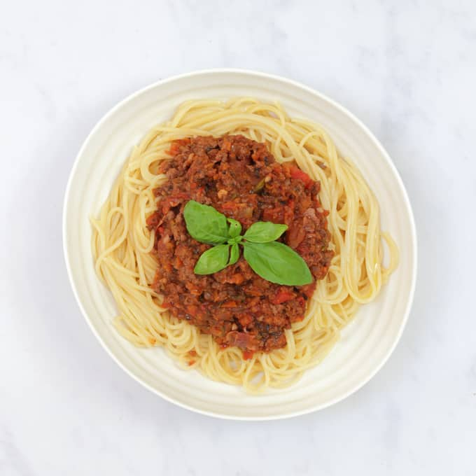 Bolognese sauce with hidden vegetables on top of pasta, garnished with a basil leaf in a white circular bowl.
