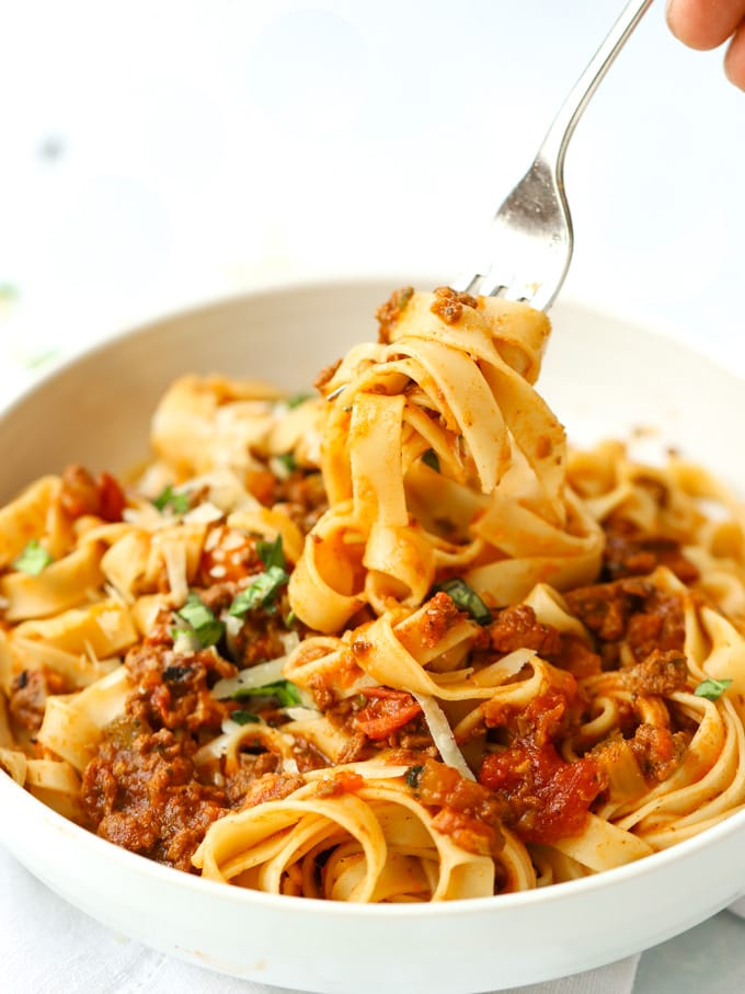 A fork lifting spaghetti bolognese from a bowl