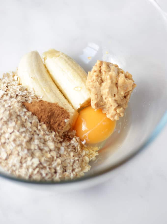 Oats, bananas, egg and peanut butter with cinnamon in a glass bowl on a white background.