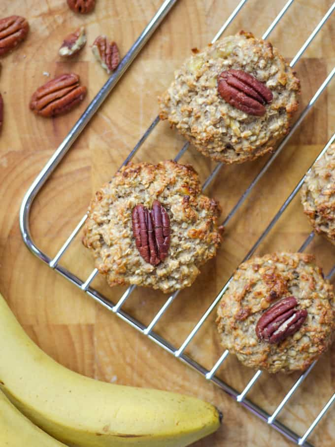 Oat based cookies topped with pecans on a wire cooling rack, with a wooden board and with unpeeled bananas.
