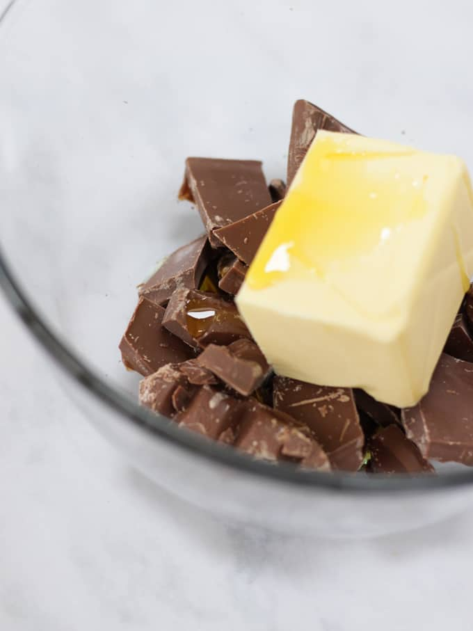 A glass bowl with chocolate chunks, a block of butter and golden syrup in.