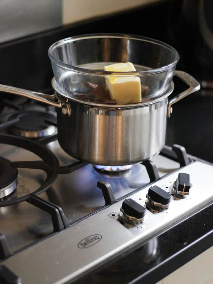 A saucepan on a gas hob topped with a glass bowl with chocolate and butter and golden syrup in to melt in a Bain Marie.