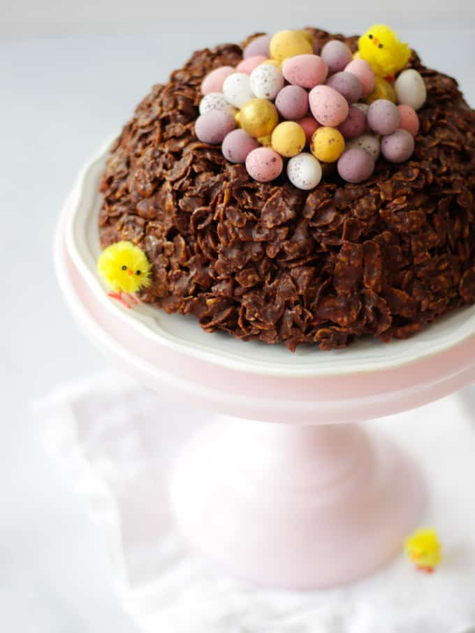 Giant Easter nest cornflake cake, circular with Mini eggs in the centre, small fake yellow chicks on a white plate and a pink stand.