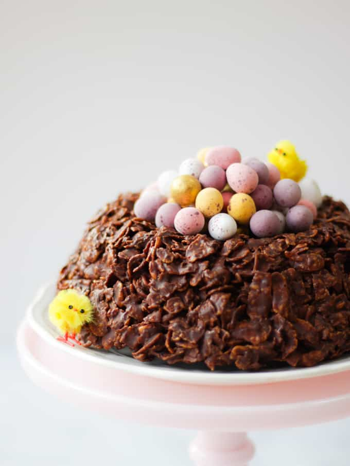 Easter chocolate cornflake cake giant next with mini eggs and Easter chicks on a pink stand. side view.