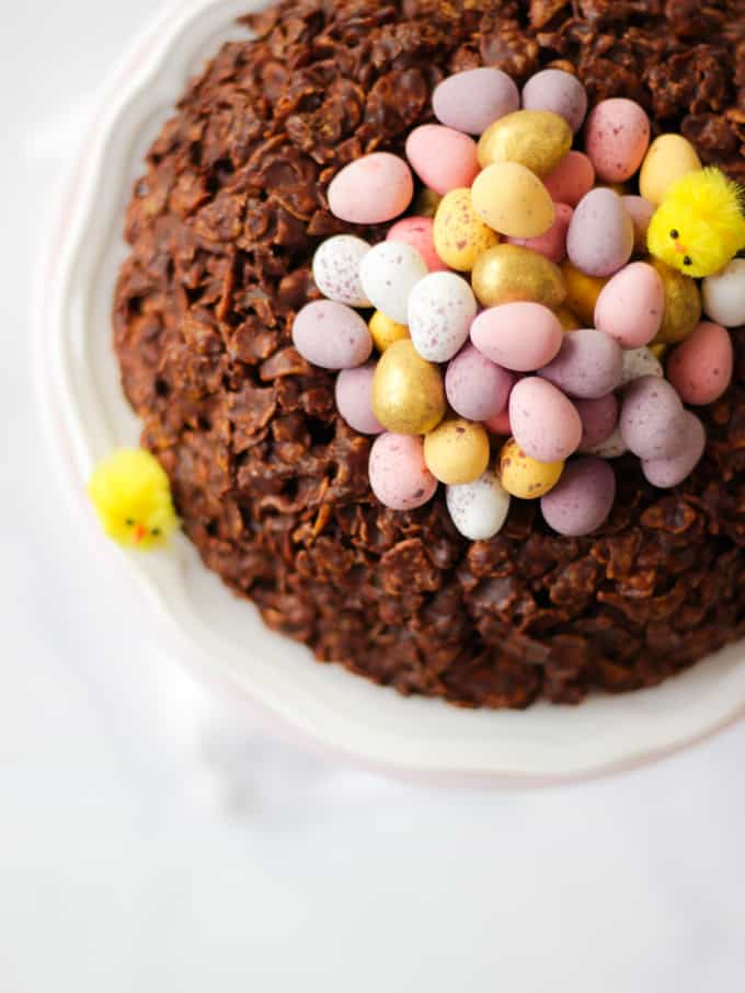 Overhead view of a giant Easter next cornflake cake with mini egg chocolates in the centre.