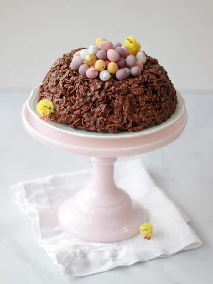 Pink tall milk glass cake stand with chocolate cornflake cake Easter next on with white napkin.