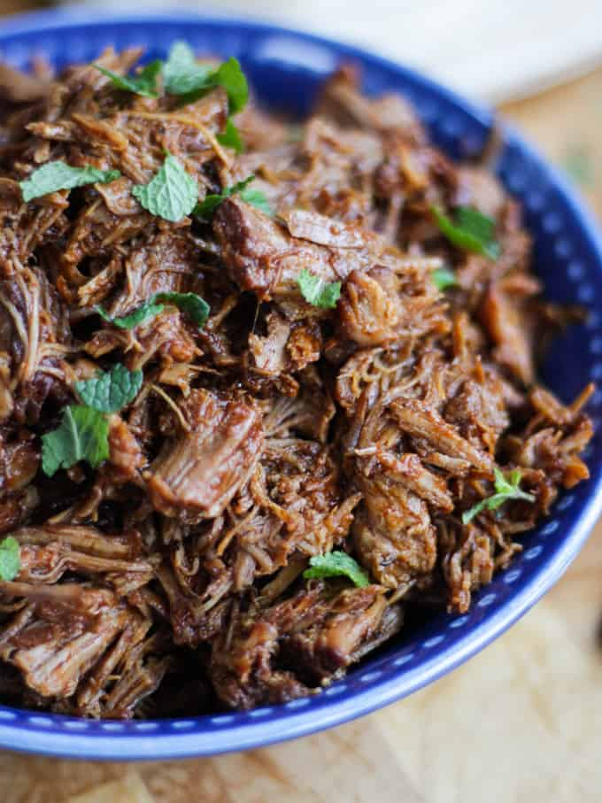 Side view of instant pot pulled pork sprinkled with mint in a blue bowl.