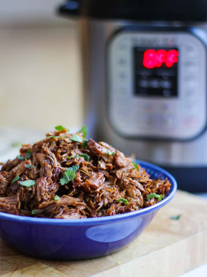 Blue bowl full of instant pot pulled pork with instant pot in background.