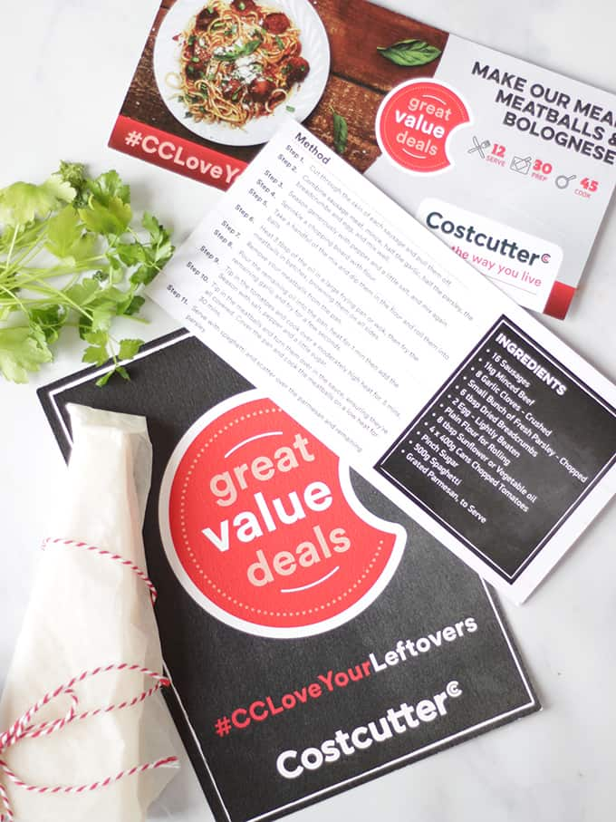Recipe cards for spaghetti and meatballs from Costcutter with Parmesan and parsley on white marble background.