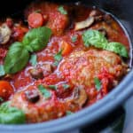 Side view of slow cooker chicken cacciatore with tomatoes and basil leaves.