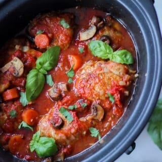 Overhead view of slow cooker chicken cacciatore with basil leaves and white background