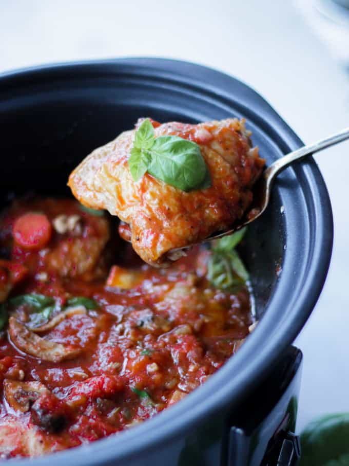 Cooked chicken thigh lifted from a slow cooker chicken cacciatore, with basil leaf on top.