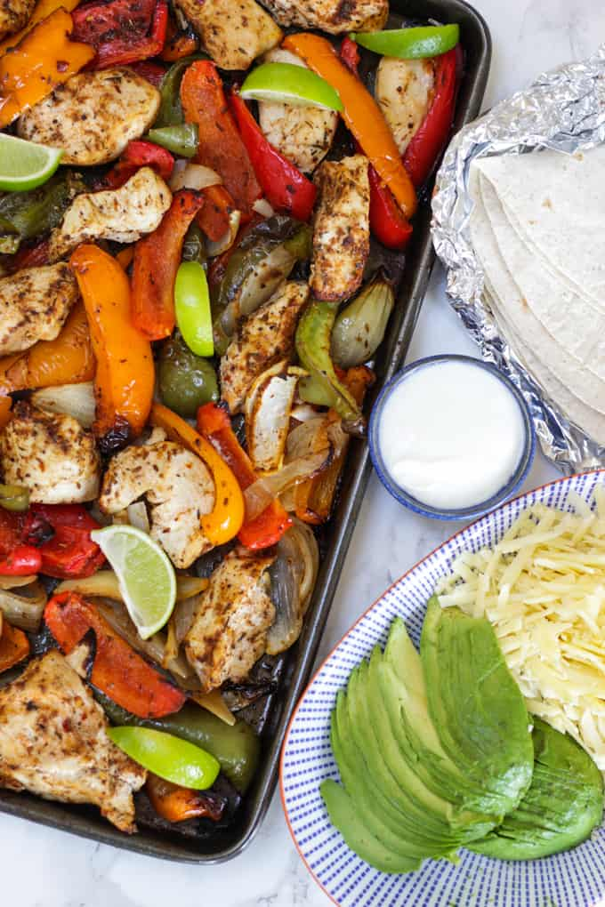 Oven baked chicken fajitas on a baking tray with peppers and lime wedges and avocado and cheese on a blue striped plate.